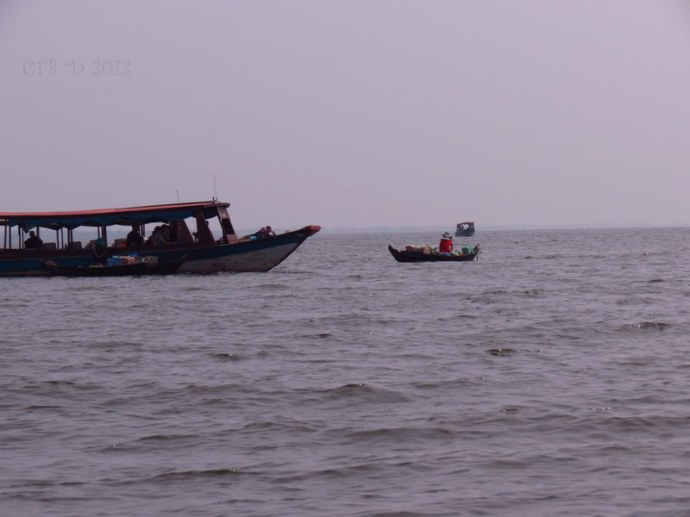a tourist boat with approaching sellers out on Tonle Sap Lake